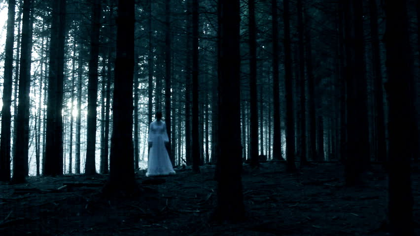 Mysterious woman in white dress in dark spooky forest