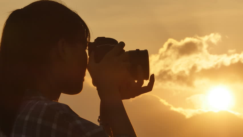 Silhouette of Vietnamese girl photographer taking pictures against the background of evening clouds