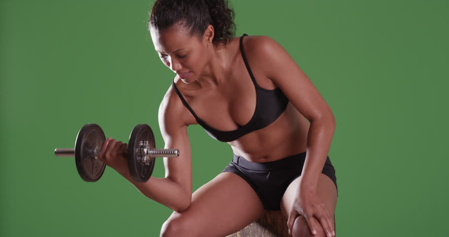 Mixed-race millennial woman\xE6lifting weights on green screen. On green screen for keying or compositing.