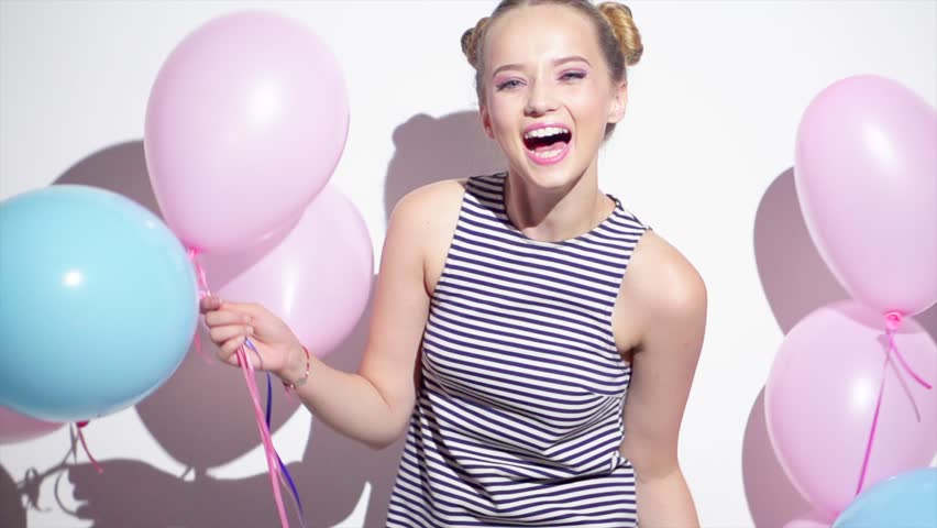 Beauty girl with colorful air balloons spinning and laughing, on white background. Beautiful Happy Young woman on birthday holiday party. Joyful model having fun, celebrating. 4K slow motion video | Shutterstock HD Video #30068428