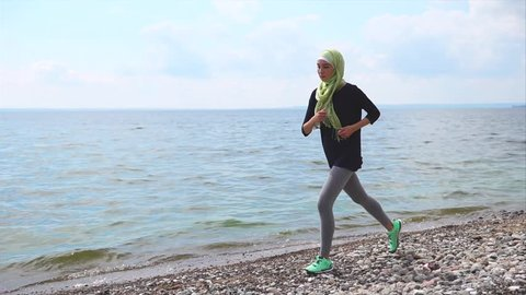 Slow motion steadicam shot of Muslim girl having sports training outdoor. She wearing green hijab and sportswear and running on pebble shore