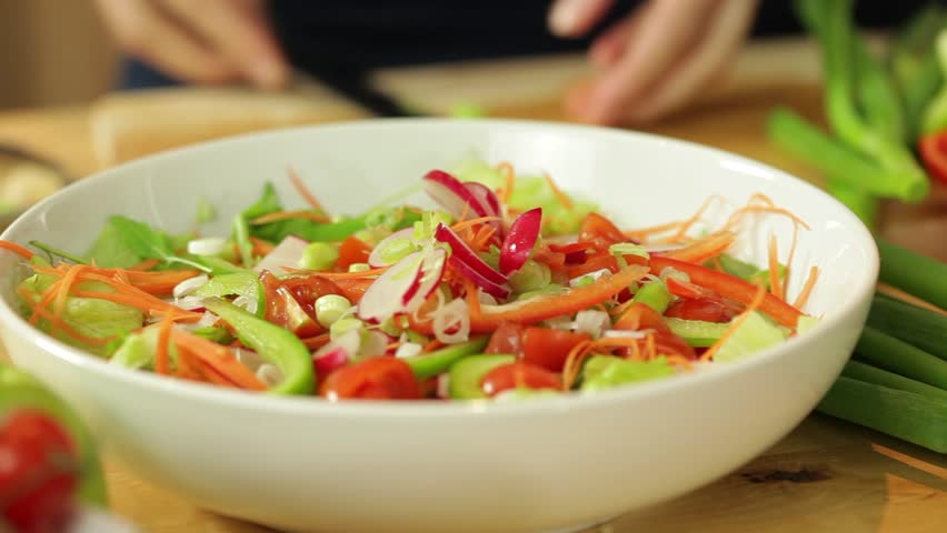 Dolly shot of female hands putting slices of vegetables into bowl in kitchen surrounding  #3009466