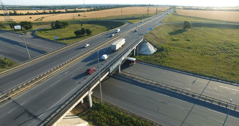 Aerial video. A beautiful, white, clean truck pulls over the clover bridge.  real time