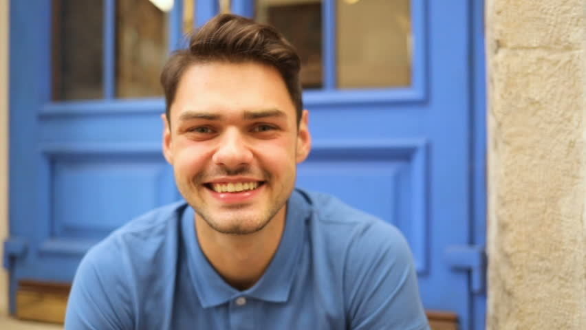 Portrait of a happy handsome young man smiling and looking at camera in a urban street. On the background are blue doors. Blue t-shirt | Shutterstock HD Video #30101488