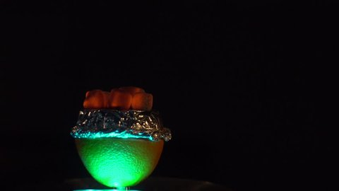 Composition of the colourfully lightning bowl full of pieces of hookah coals at the black background.