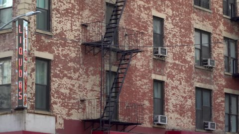 Typical urban apartment building DX exterior day establishing shot above generic liquor store front sign. Fire escape hugs facade