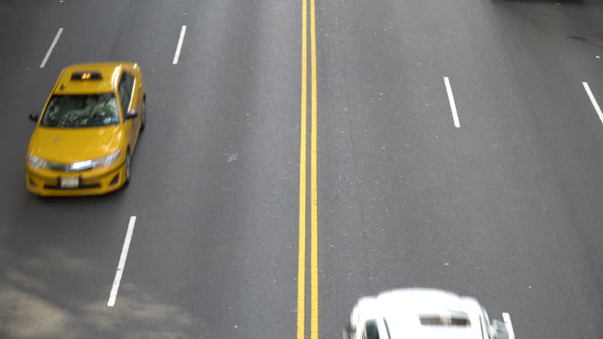 View straight down overhead busy city street two lane road as cars drive pass below overpass. Aerial type camera view