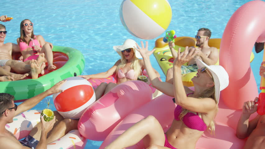 SLOW MOTION CLOSE UP Happy smiling students have water gun fight on colorful floaties at pool party on spring break. Cheerful young people have fun on inflatable flamingo pizza watermelon and doughnut