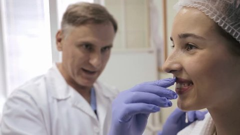 The Doctor examines Face of Woman Patient before a Cosmetic Surgery on the Nose