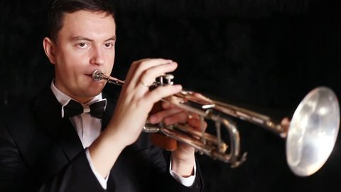 Man is playing on trumpet moving from side to side in a black room