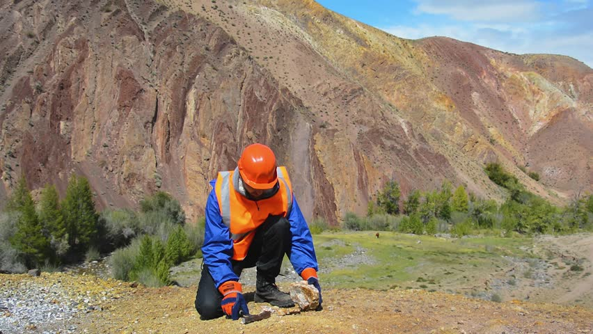 Hammering with a geologists hammer on stone. A geologist or a mining engineer wearing protective gloves with a hammer in his hand. | Shutterstock HD Video #30132238