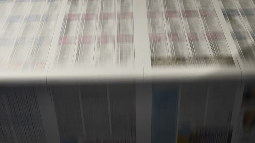 close up on newspapers being folded mechanically on a conveyor belt in a printing press.