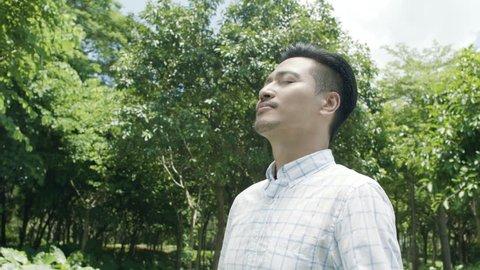 asian man taking deep breath, smiling & enjoying nature outdoor in slow motion