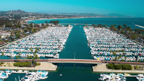 4K aerial timelapse of the Dana Point harbor in Orange County, California with luxury boats and yachts on a sunny blue sky day crossing the harbor bridge.