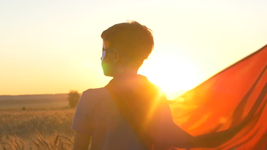 A boy with a cape of a superman stands in the golden fields of wheat looking at the horizon