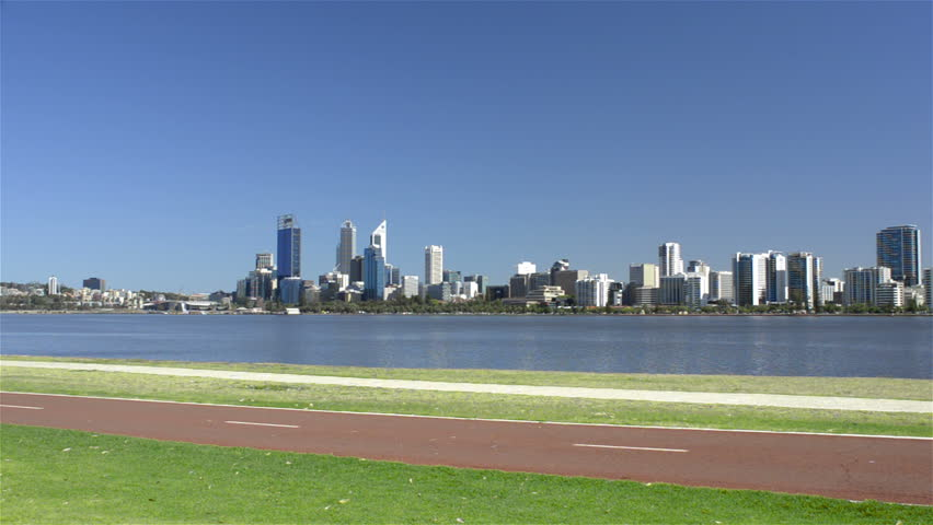Cyclists riding along a bike path along the edge of the Swan River, with Perth