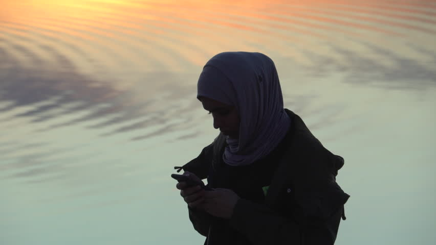 Silhouette shot of muslim woman with smart phone.Cape Town,circa August 2017 | Shutterstock HD Video #30204598
