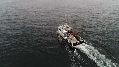 A cool aerial shot of professional fishermen catching lobster on their commercial fishing boat off the coast of Nova Scotia Canada