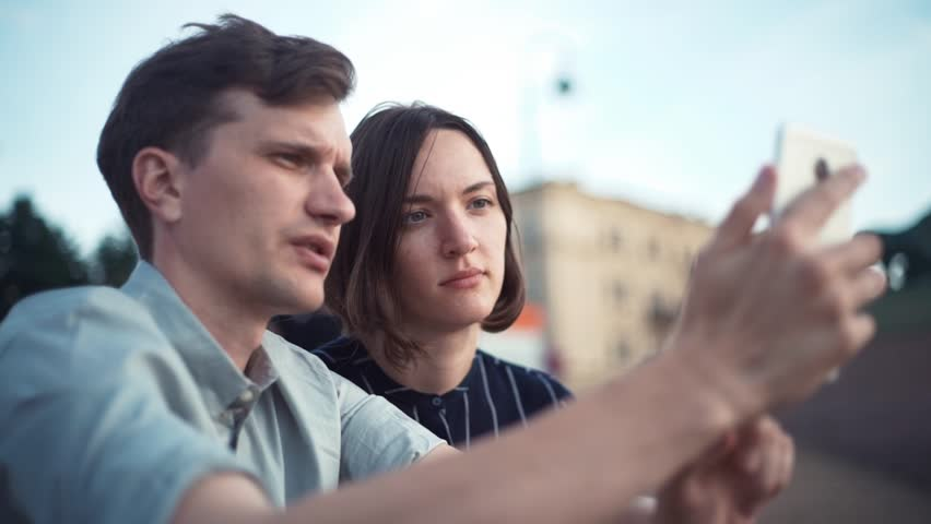 Young millennial couple watching videos on smartphone together in the park. Young couple using smartphone together outdoor in the city. #30221098