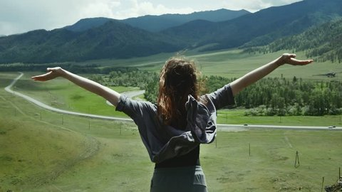 A beautiful girl reaching the top of the mountain, raises her hands and looks at the landscape.