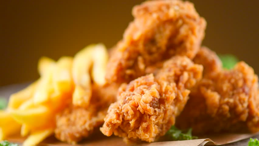 Crispy fried chicken wings and legs with french fries on a wooden table rotation 360 degrees. Breaded Crispy chicken,  fried potato tasty dinner. 4K UHD video footage. Ultra high definition 3840X2160