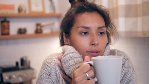 575f1051f Attractive Young Mixed Race Woman in Winter Sweater Drinking Hot Tea from  White Mug at the