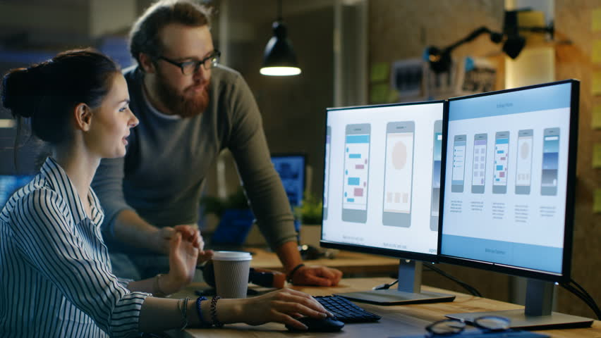 Female UX Architect Has Discussion with Male Design Engineer, They Work on Mobile Application Late at Night, She Drinks Coffee. In the Background Wall with Project Sticky Notes. 4K UHD.  | Shutterstock HD Video #30236188