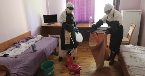 Two unrecognizable doctors or nurses wearing full Ebola virus protection uniform disinfect room after evacuation of patient.  Danger of infection and epidemic. 4K footage.
