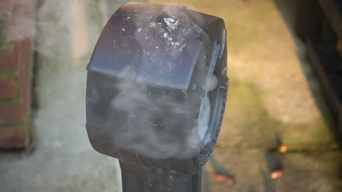 A plastic smokers receptacle with burning smoke