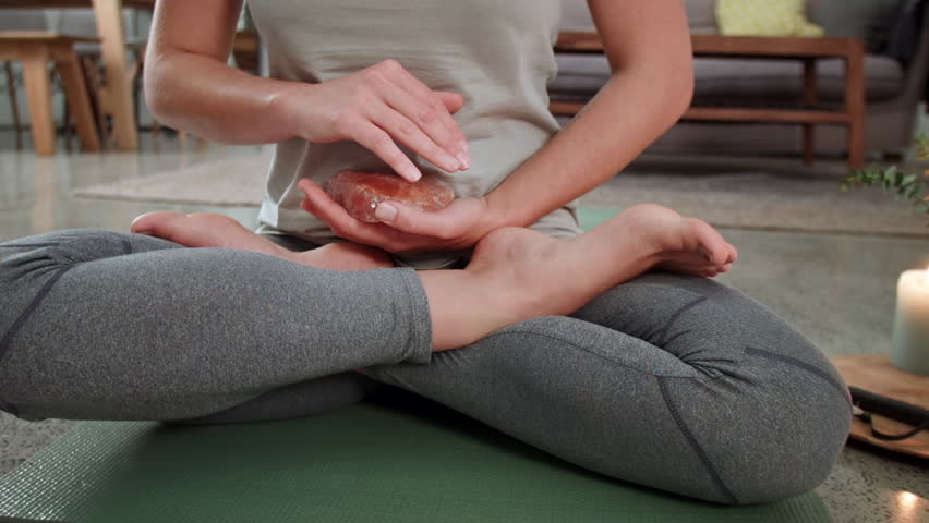 Anonymous woman cradles quartz crystal during meditation session, believing in crystal healing calming energy properties
