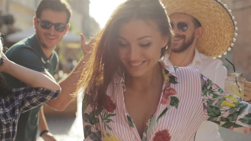 Multirace interracial mexican theme party concept - attractive turkish latina european people dancing on the city street, lens flare sun shining