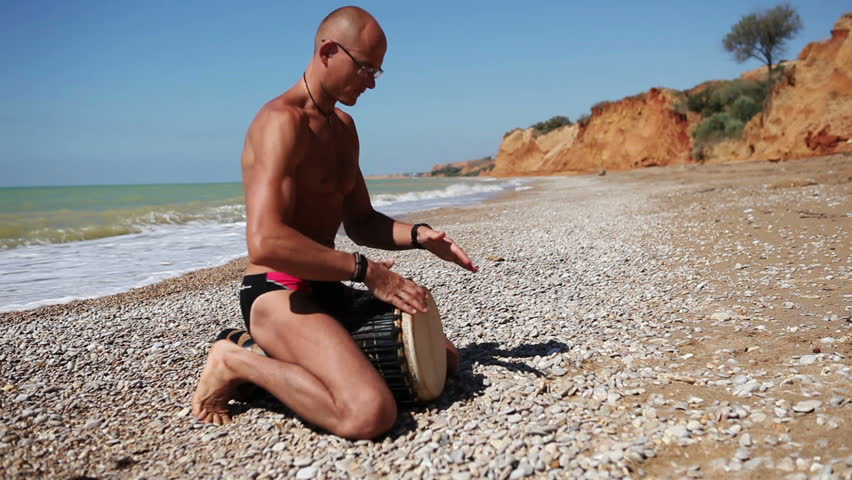 Djembe traditional Drum Player beat rhythm on the lonely beach