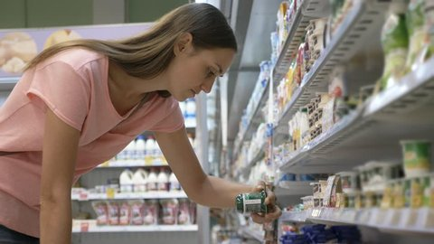 Young housewife in summer wear selecting dairy products in fridge at grocery department of shopping mall