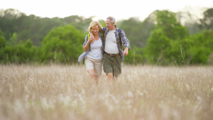 Active senior Caucasian American couple wearing casual clothing on hike enjoying their walking outdoors RED DRAGON