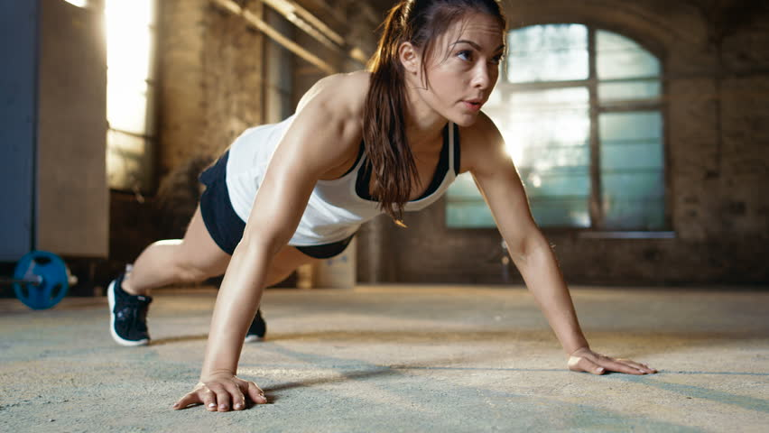 Athletic Beautiful Woman Does Push-ups as Part of Her Cross Fitness, Bodybuilding Gym Training Routine. Shot on RED EPIC-W 8K Helium Cinema Camera.