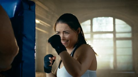 Athletic Woman Hits Punching Bag that Her Partner/ Trainer Holds. She's Professional Fighter and is Training in a Gym. Shot on RED EPIC-W 8K Helium Cinema Camera.