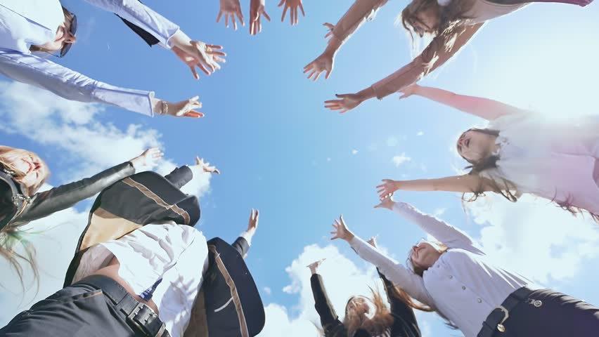 Friendly graduates of the senior school put their hands on each other and open them against the blue sky. Sunny daylight. College Students Teamwork Stacking Hand Concept.