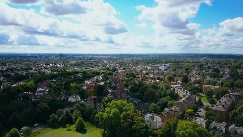 Aerial view of a leafy UK suburb on a summers day - camera tracks left