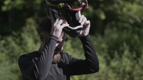 Mountain biker takes of helmet to enjoy the sunshine in 4k