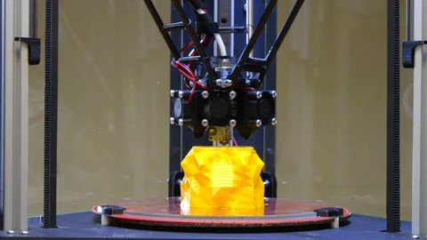 3d printing printer bright yellow model close-up. Automatic 3D printer performs plastic modeling in laboratory. Modern additive technologies, 4.0 industrial revolution. Timelapse