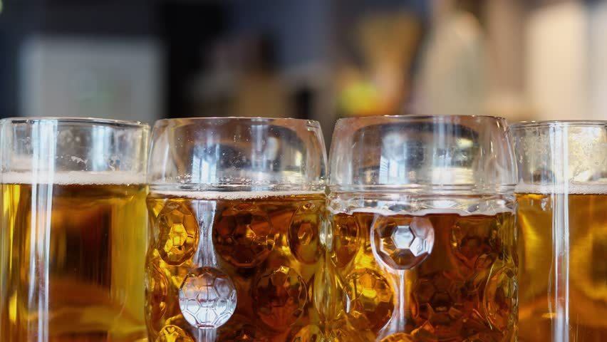 Bubbles ascend in four glass jars full of beer with scum