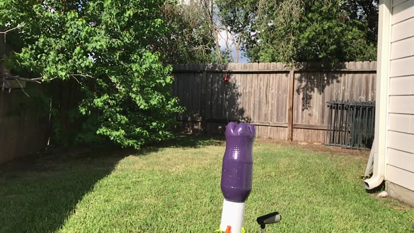 Slow motion of water bottle rocket blasting off and streaming water #30370348