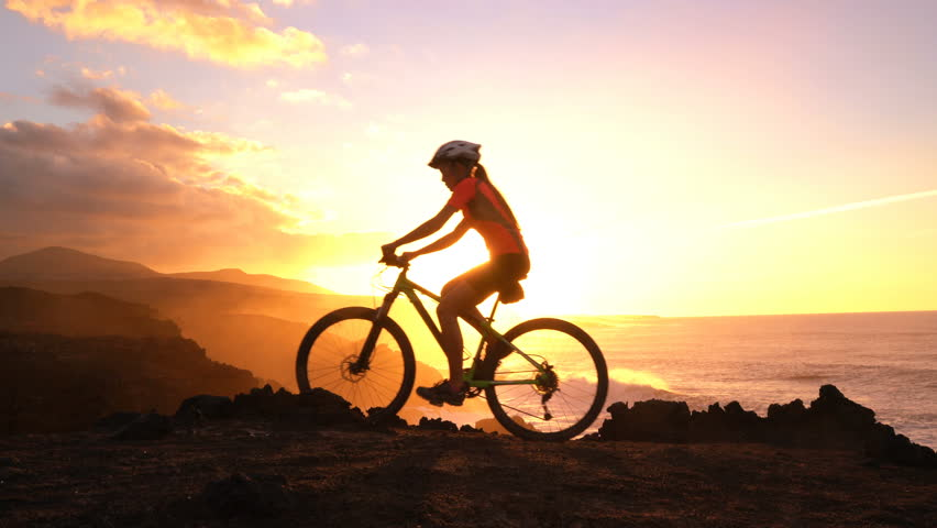 Mountain biking MTB cyclist woman cycling on bike trail at sunset by ocean. Person on bike by sea in sportswear with bicycle enjoying healthy active lifestyle in beautiful nature outside. | Shutterstock HD Video #30373798