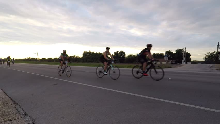 The Wichita Falls bicycle 100 mile race. Wichita Falls, Texas - August 26, 2017. POV. point view of group of cyclists on the road in the early morning.