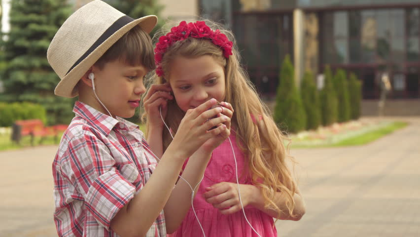 Attractive little children watching something on smartphone outdoors. Two nice caucasian kids sharing earphones among themselves. Handsome brunette boy holding celphone in his hands | Shutterstock HD Video #30401248