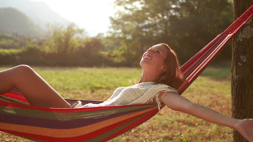 young woman relaxing on hammock arms outstretched beautiful woman on hammock surrounded by nature   young woman relaxing on hammock arms outstretched young woman      rh   shutterstock