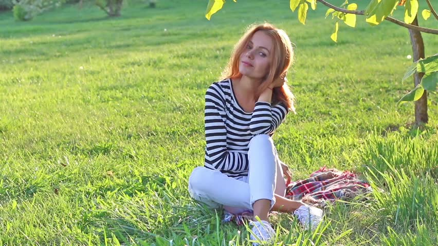 Young beautiful fashion hipster woman portrait sensually enjoying the sunset in summer park, sitting on grass, smiling and touching long blonde hair, in striped shirt and white jeans