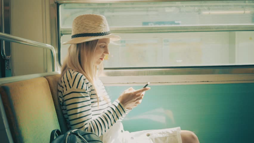 Woman tourist sitting at train and looking to mobil phone near the Eiffel tower at sunny day in Paris. Famous popular touristic place in the world. | Shutterstock HD Video #30411388
