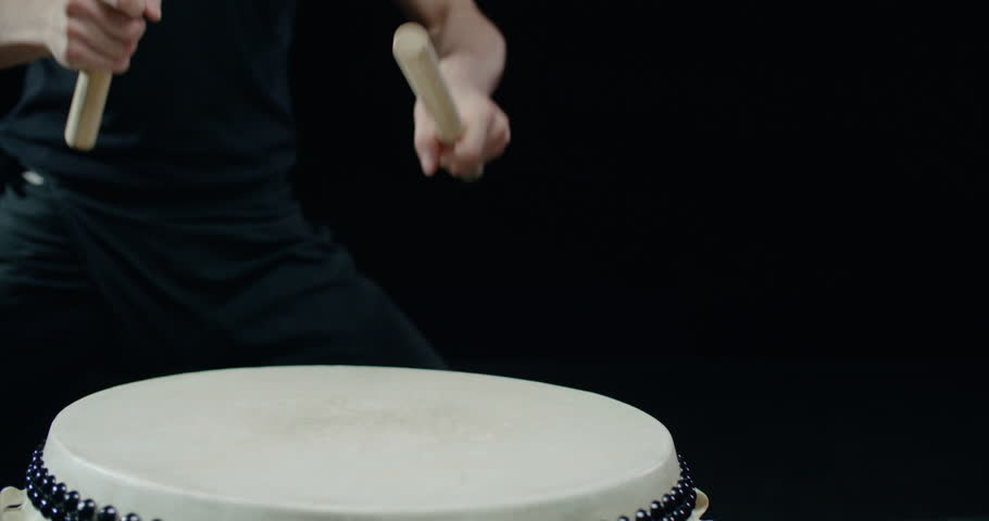 performance of Taiko , a detail shot Asian male drummer in black clothes, beats a rhythm on a Japanese drum,black background