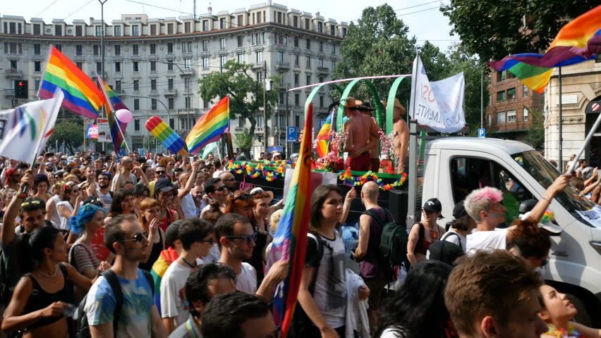 MILAN, ITALY – JUNE 24: People march holding rainbow flags at Milano pride parade in Milan, Italy on June 24, 2017